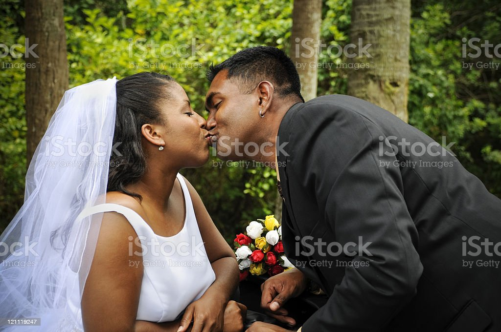 Diverse Couple Sharing a Wedding Kiss stock photo