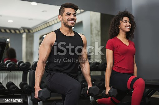 Training together. Diverse couple doing lunges with dumbbells in gym, copy space