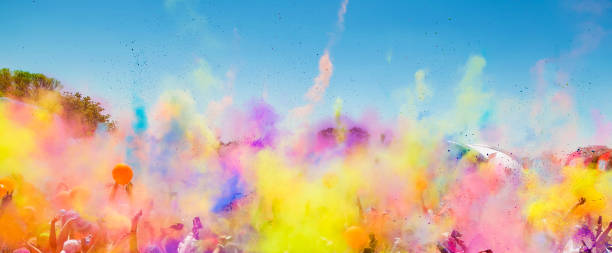 Diverse Crowd throwing bright colored powder paint in the air at Holi Festival Diverse Crowd throwing bright colored powder paint in the air at Holi Festival Dahan event colored powder stock pictures, royalty-free photos & images