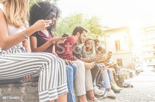 istock Diverse culture friends using smartphones outdoor 867104950