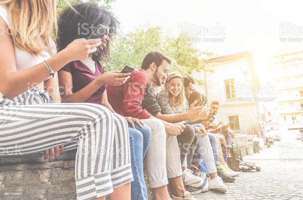 Amis de diversité culturelle à l'aide de smartphones en plein air - Photo
