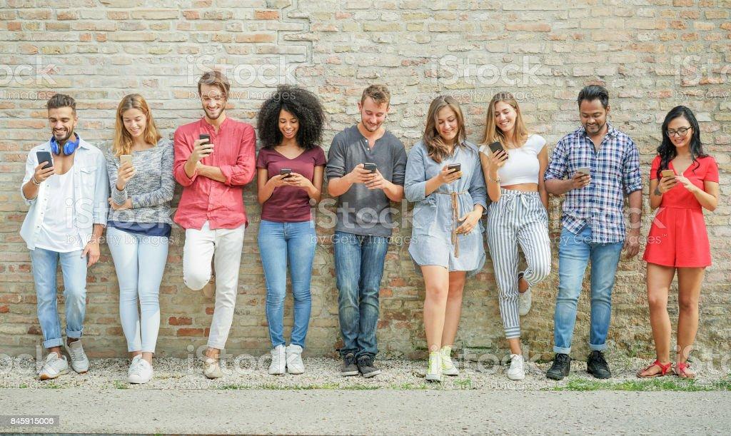 多様な文化の人々 は友人を使用して携帯電話スマート フォン屋外 - 幸せな技術動向 - 若者、新世代中毒と友情概念を楽しんで - 暖かいフィルター ロイヤリティフリーストックフォト