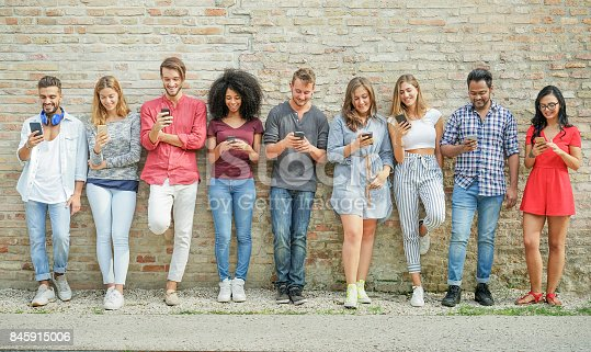 istock Diverse culture people using mobile smartphone outdoor - Happy friends having fun with technology trends - Youth, new generation addiction and friendship concept - Warm filter 845915006