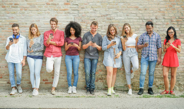 Diverse culture people using mobile smartphone outdoor - Happy friends having fun with technology trends - Youth, new generation addiction and friendship concept - Warm filter - foto stock