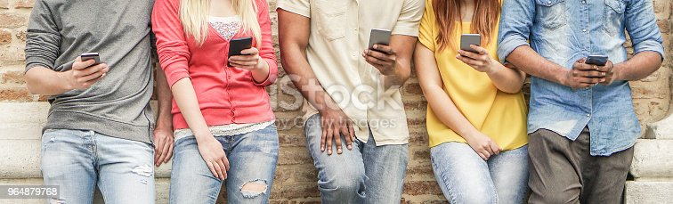 istock Diverse culture students watching smart mobile phones in university break - Young people addiction to new technology trends - Alienation moment for new generation problem - Focus on center hands 964879768