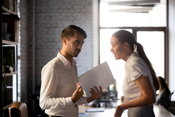 Diverse employees argue over financial report in office Millennial diverse employees standing holding financial paperwork, disputing over statistics or contract terms, man and woman have misunderstanding in office, argue or quarrel on document or report confrontation stock pictures, royalty-free photos & images