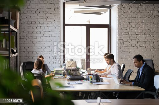 1090214584 istock photo Diverse employees busy working in shared office 1129819879