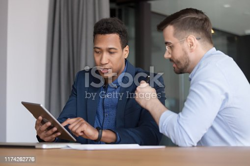 863497390 istock photo Diverse employees discuss new business app on tablet device 1174262776