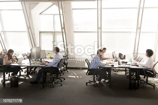 1090214584 istock photo Diverse employees focused on working on desktops in shared office 1070271776