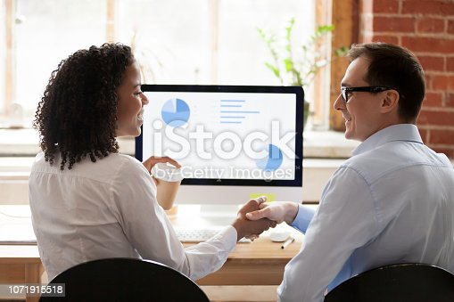 843963182 istock photo Diverse employees handshake working together at pc in office 1071915518