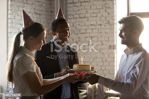 istock Diverse employees in party hats holding gifts congratulating coworker 1085714036