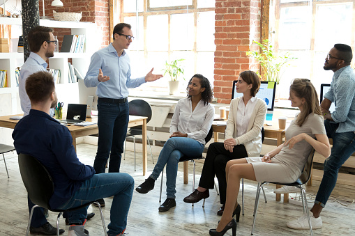 Diverse Employees Listening To Male Manager Speaking At Group Meeting Stock Photo - Download Image Now