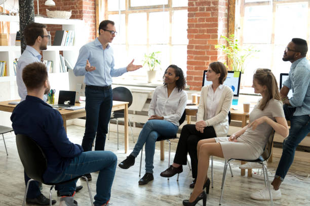 Diverse employees listening to male manager speaking at group meeting stock photo