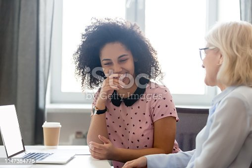 1166905017 istock photo Diverse employees sitting at desk laughing take break from work 1147384775
