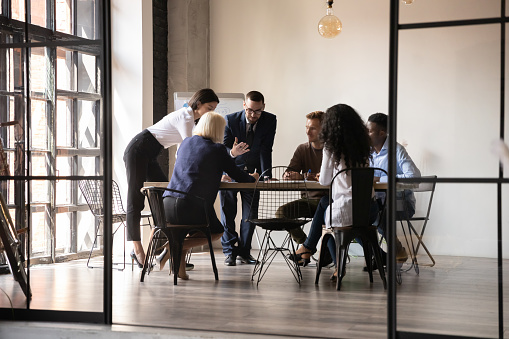 Diverse employees team engaged in teamwork in modern boardroom, sitting at table in office, reading legal documents, analyzing project statistics, financial report, discussing strategy, planning