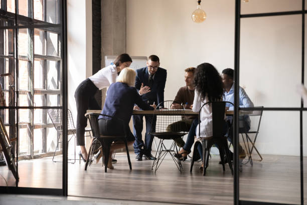 Diverse employees team engaged in teamwork in modern boardroom stock photo