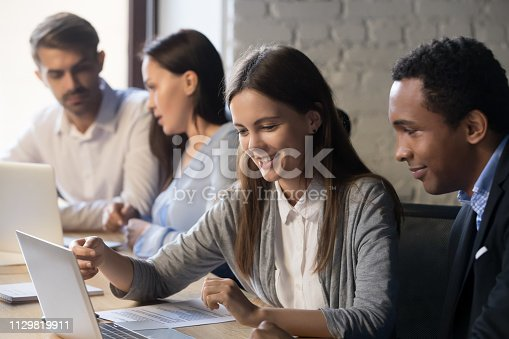 Diverse employees sit at shared office table busy at laptop, discussing business project together, confident millennial female worker explain issues to black colleague, men and women cooperating