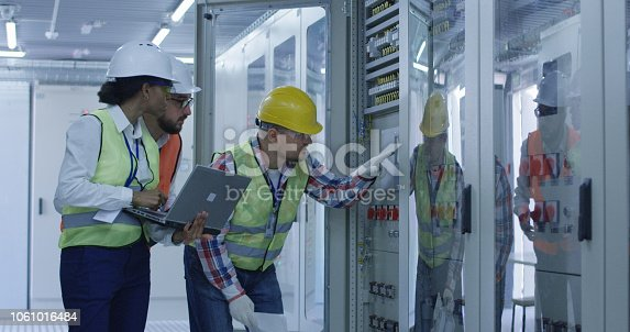 Group of multiethnic men and woman in hardhats working in hall of solar plant control center having discussion between racks