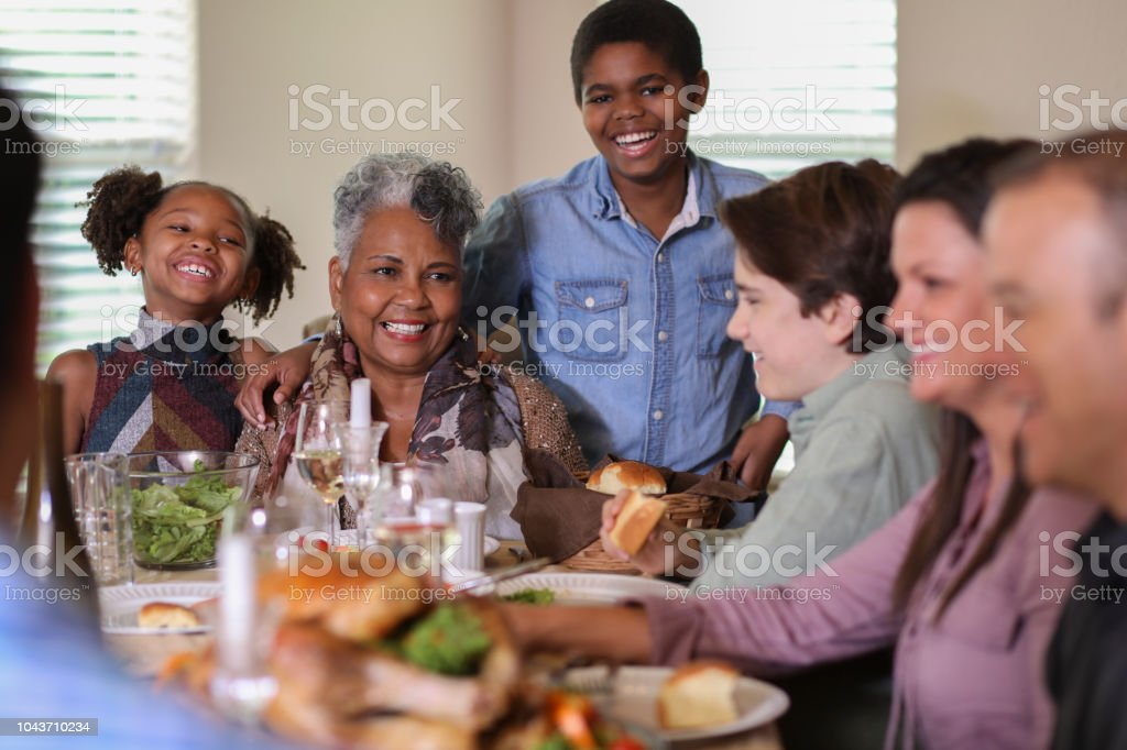 Diverse Family At Dining Table Eating Thanksgiving Dinner Stock