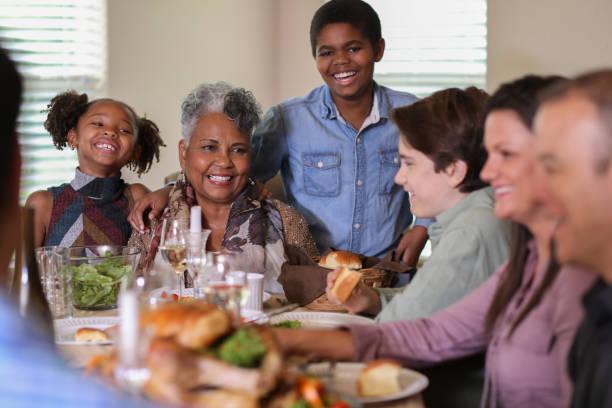 Vielfältigen Familie am Esstisch Essen Thanksgiving-Dinner. – Foto
