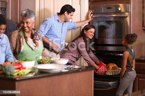 Multi-ethnic family members work together in grandmother's home kitchen to prepare Thanksgiving dinner.  Hispanic, African and Caucasian ethnicities.  Roasted turkey, vegetable food items.