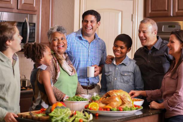 diverse family in home kitchen cooking thanksgiving dinner. - kolacja spotkanie towarzyskie zdjęcia i obrazy z banku zdjęć
