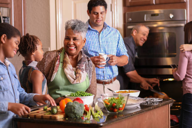 Diverse family in home kitchen cooking Thanksgiving dinner. stock photo