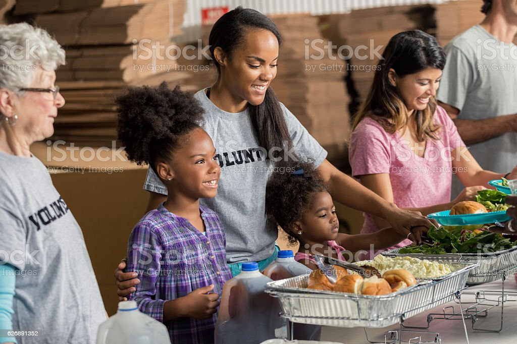 Diverse family volunteers together in soup kitchen stock photo