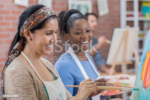 istock Diverse female friends paint together during art class 658645980