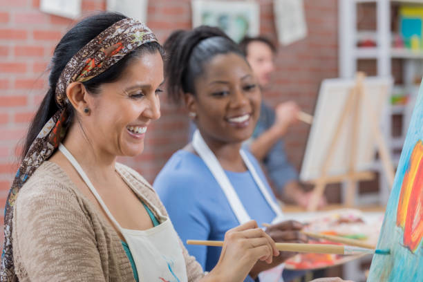 Diverse female friends paint together during art class stock photo