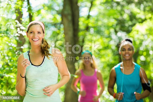 1051098428 istock photo Diverse female runners jogging together in park 480560664