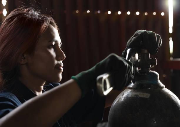 diversa ingeniera de taller femenina ajustando válvulas en tanques de gas - suministros escolares fotografías e imágenes de stock