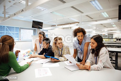 Teacher with a group of university students, in a laboratory classroom. The instructor is considering one of the students work, the mood is light hearted and positive. Other classmates are discussing things with each other. This is a realistic teaching scenario, with candid expressions. This is a multi-ethnic group of women. In the background there is a white board with mathematical formula written on it. All ladies are wearing id tags.