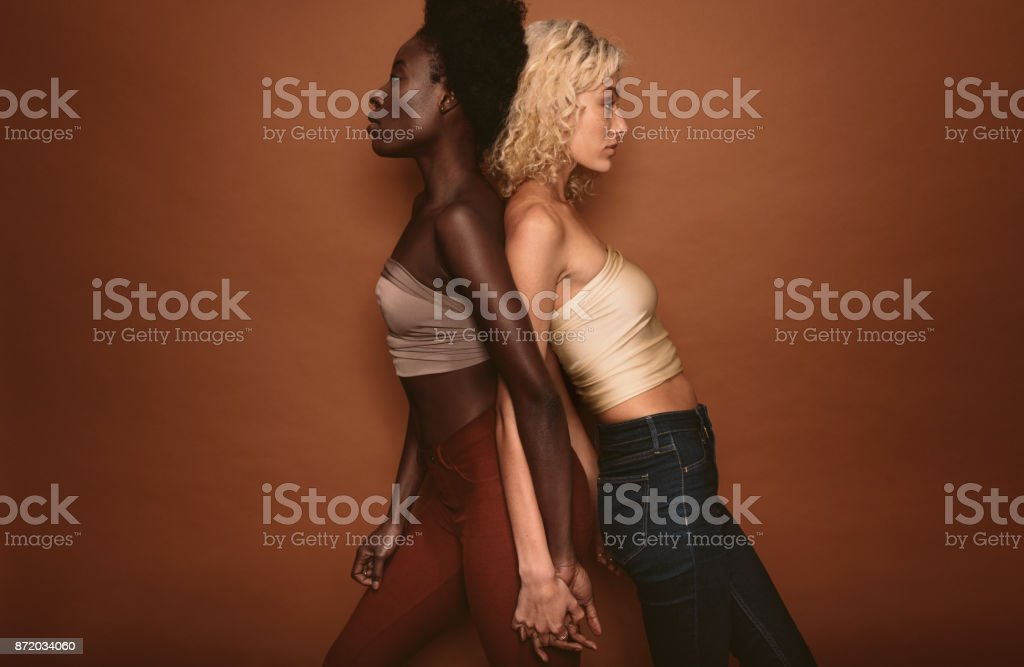 Diverse females standing on brown background stock photo