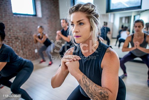 Diverse group of young adults doing squats in unison during a fitness class