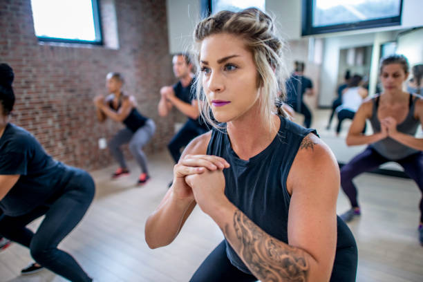 Diverse fitness class doing squats Diverse group of young adults doing squats in unison during a fitness class exercise class stock pictures, royalty-free photos & images