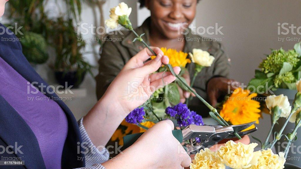 Diverse florists prepare floral arrangements stock photo