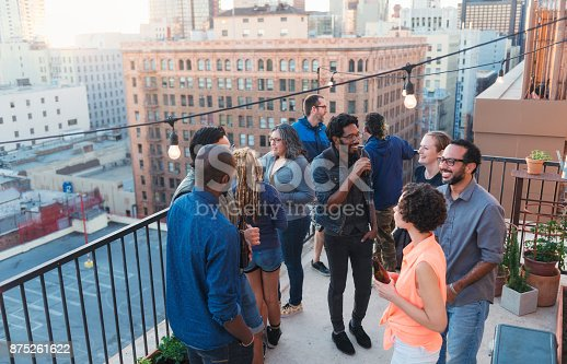 istock Diverse friend group having roof party 875261622