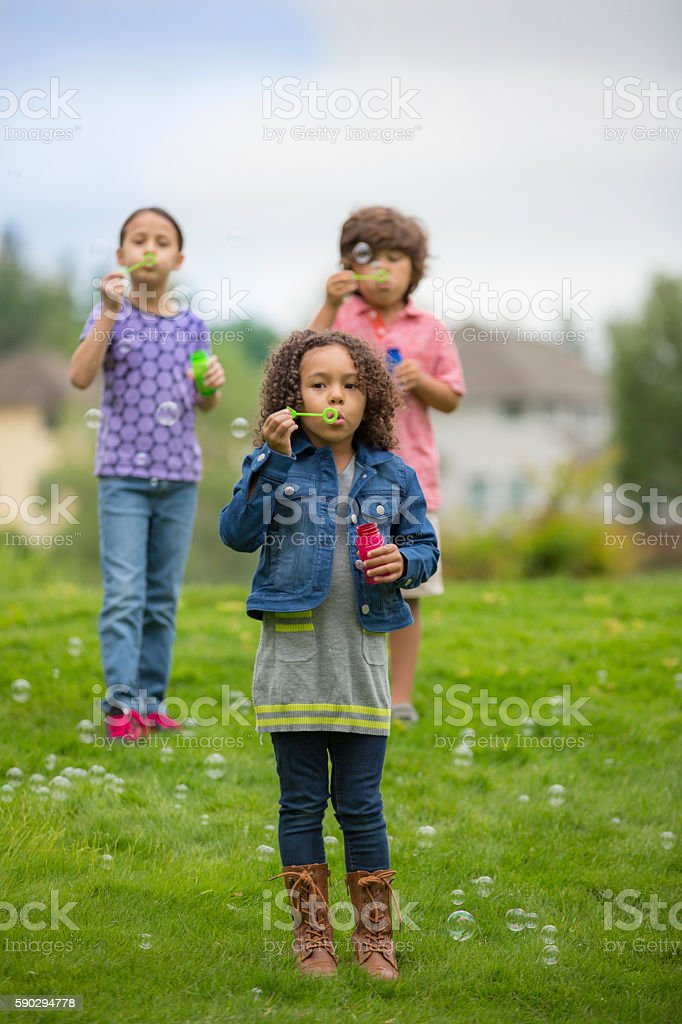 Diverse friends blowing bubbles royaltyfri bildbanksbilder