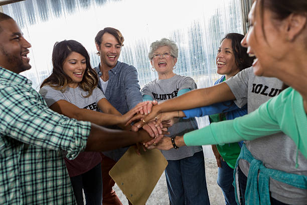 Diverse friends cheer before beginning volunteering at food bank stock photo