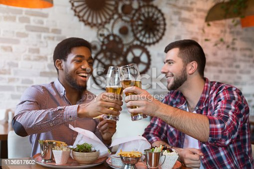 istock Diverse friends drinking beer and eating burgers 1136617602