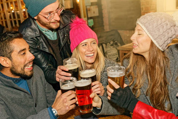 Diverse Friends Hanging Out Together Group of smiling happy friends drinking beer and having fun together Multi-ethnical friends enjoying time together at the bar Smiling Girl drinking beer stock photo