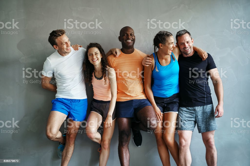 Diverse friends in sportswear laughing together in a gym royalty-free stock photo