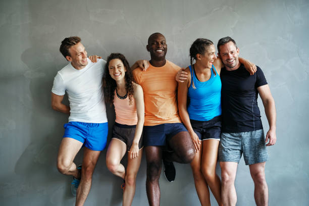 Diverse friends in sportswear laughing together in a gym stock photo