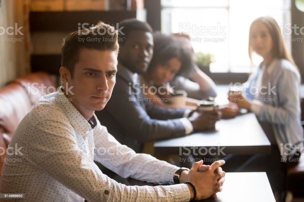 Diverse friends looking at frustrated man sitting alone in cafe stock photo