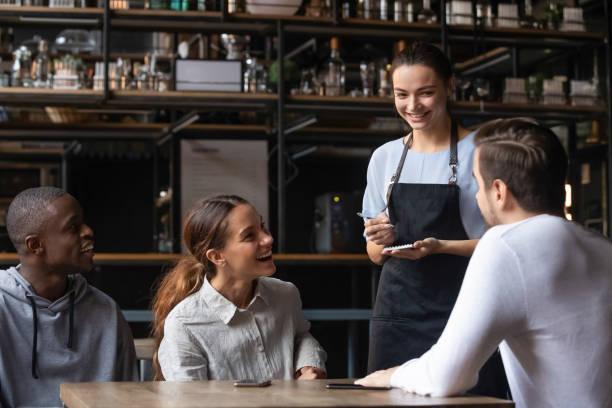 diverse freunde sitzen im restaurant und bestellen mit kellnerin - bestellen stock-fotos und bilder