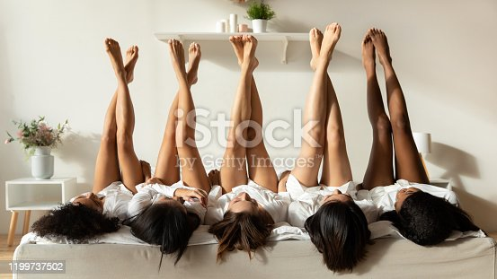 Diverse millennial girls lie upside down show legs celebrate bridal shower at home together, multiracial female friends in bathrobes have fun at spa pajama hen party in hotel, depilation concept
