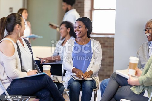 487670635istockphoto Diverse group enjoys a laugh during meeting 1168467740