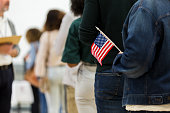 istock Diverse group in line to vote; one holds American flag 1203196350