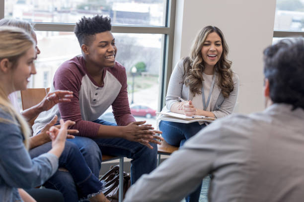 Diverse group laughs when unseen person tells a joke stock photo
